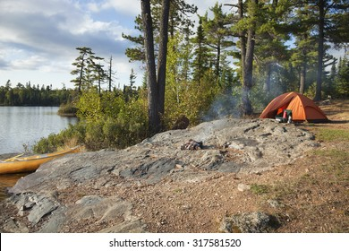 Campsite with orange tent and canoe on a lake in the Boundary Waters Canoe Area Wilderness of Minnesota