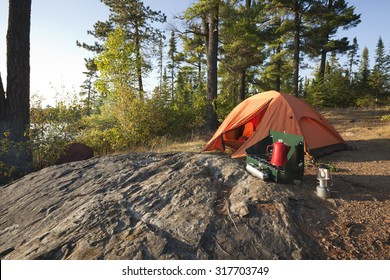 A campsite with an orange tent and cook stove in the north woods of Minnesota