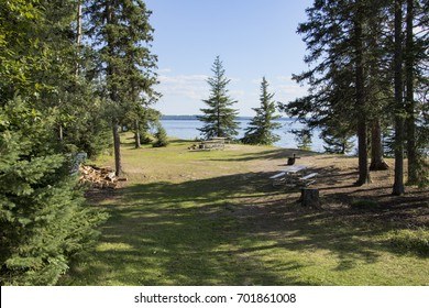 Campsite with picnic and campfire areas next to the hiking trail to Grey Owl's cabin on the shore of Waskesiu Lake in Prince Albert National Park in Saskatchewan Canada.