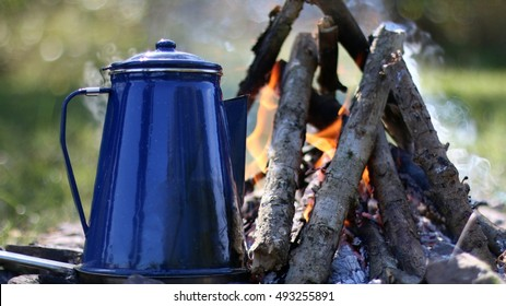 Campsite With Small Burning Campfire And Blue, Metal Coffee Pot Heating In Coals With Morning Sunlight Glistening In Background On A Farm In The Mountains Of South West Virginia