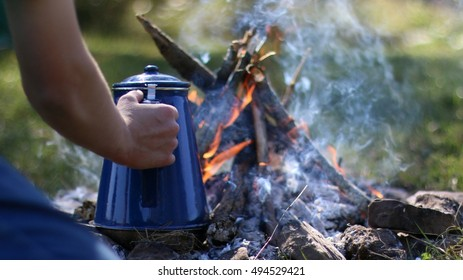 Campsite With Small Burning Campfire And Camper Heating Coffee In Blue Coffee Pot With Smoke Glistening In Morning Sunlight In The Mountains Of South West Virginia