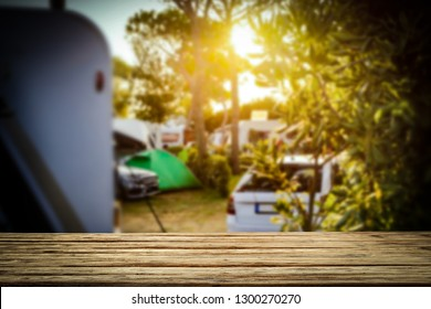 A campsite in a sunny place with a wooden board for an advertising product