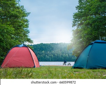 Campsite with tents at a lake, with woods in background