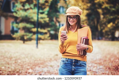 Campus life. Young smiling girl typing a message on a mobile phone while holding folders and books in a hand. Education, fashion, lifestyle concept