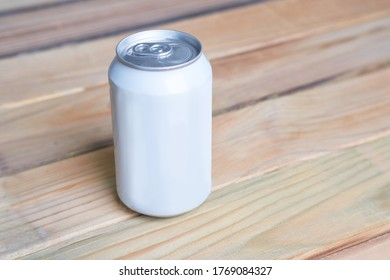 A can of beer is on the board