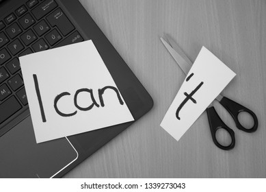 I can, I can't. White paper, notebook and scissors on a desk with a message I can