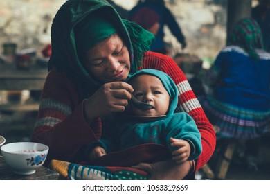 Can Cau market, Bac Ha, LAOCAI/ VIETNAM - January 2 2016: A H'mong woman feeding her son to eat breakfast in Can Cau market.