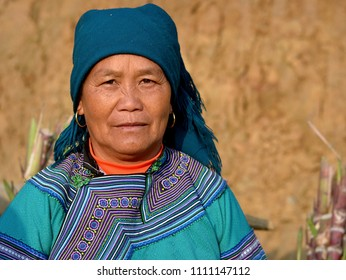 CAN CAU, VIETNAM - MARCH 10, 2018: Elderly Vietnamese Flower H'mong hill-tribe woman in blue traditional attire poses for the camera at Can Cau's lively Saturday market, on March 10, 2018.