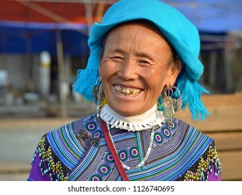 CAN CAU, VIETNAM - MARCH 10, 2018: Elderly Vietnamese Blue H'mong hill-tribe woman with three gold teeth wears traditional H'mong embroidery in blue and smiles for the camera, on March 10, 2018.