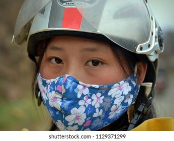 CAN CAU, VIETNAM - MARCH 24, 2018: Young Vietnamese scooter girl wears a motorcycle crash helmet, hides her nose and mouth behind a protective face mask and poses for the camera, on March 24, 2018.