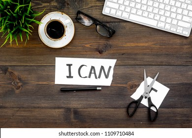 I can concept. Encourage youself. Sciccors cut off the letter t of written word I can't. Office desk. Dark wooden background top view space for text