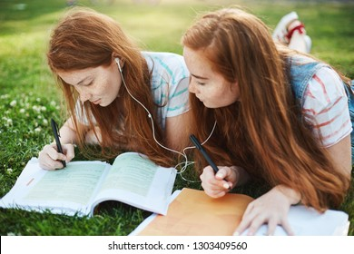 Can I copy your homework, sure but change it little. Good-looking twin sisters with freckles, sharing earbuds and lying on grass near dormitory while doing home assignment, girl checking answers
