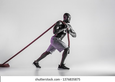 I can do anything. Young african-american bodybuilder training over grey background. Muscular single male model in sportwear pulling the battle rope. Concept of sport, bodybuilding, healthy lifestyle.