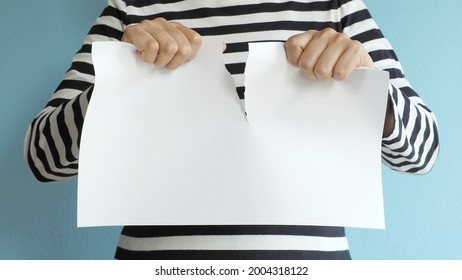 Can do attitude theme hands of woman in black and white striped t-shirt tearing blank white paper on blue background. Bending the rules concept. (close up, selective focus, space for text)