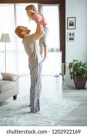 I can fly. Happy dad is lifting up his little daughter while standing in living room. Dreamful girl is wearing fairy wings and laughing