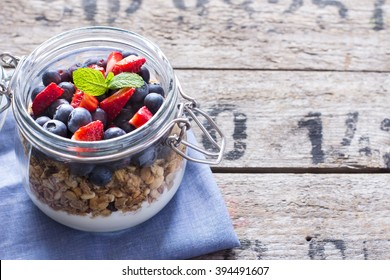 Can with granola or musli on the wooden table with copy space