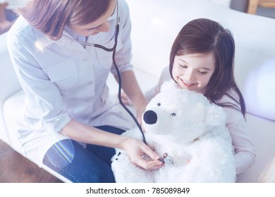 I can help him. Positive delighted nurse keeping smile on her face and bowing her head while measuring pressure of toy bear