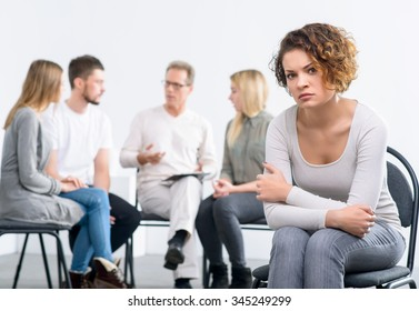Can not find the solution. Gloomy depressed young woman sitting on the char with psychologist working with people during psychological group  therapy session