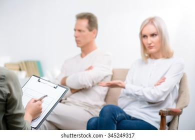 Can not live together. Selective focus of folder in hands of professional psychologist holding it and interrogating adult couple sitting on the sofa in the background