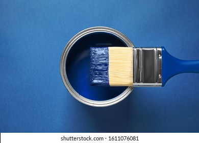 Can of paint and brush on bright background, top view. Color of the year 2020 (Classic blue)
