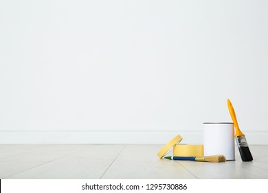 Can of paint and decorator tools on wooden floor indoors. Space for text