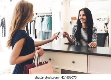 Can I pay with my card? Beautiful young woman with shopping bags giving her credit card to seller while standing at the clothing store