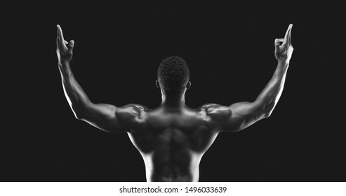 I can rule the world. African american athletic guy raising hands up in gun gesture, back view, black and white picture