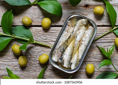 Can of sardines in olive oil and olives on rustic table