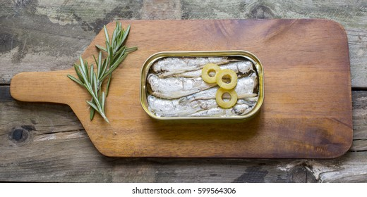 Can of sardines on a table on rustic wooden table