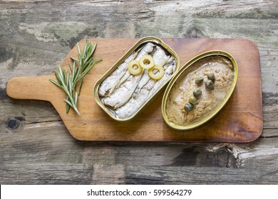 Can of sardines and tuna on a table on rustic wooden table