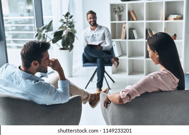 I can see a progress here! Young married couple talking while sitting on the therapy session with psychologist