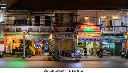 Can Tho, Mekong Delta, Vietnam, South east Asia; Feburary 2020: Street at night with shops, chinese style houses, restaurant terraces and people in the city centre of Can Tho