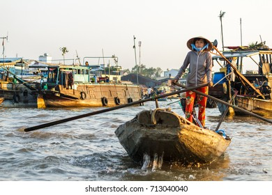 CAN THO, VIETNAM - 3/24/2016: A merchant paddles through Cai Rang Floating Market on the Mekong river to sell products to tourists.