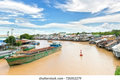 Can Tho, Vietnam - August 25th, 2017: Ships cross the confluence of riverside villages with adjacent stilts on each other like a beautiful picture of the waterfront in Can Tho, Vietnam.