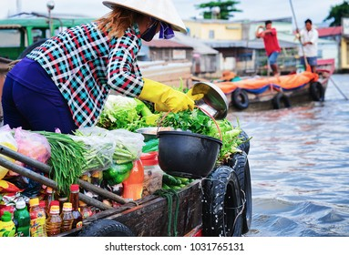 Can Tho, Vietnam - February 28, 2016: Woman in a boat selling fresh green vegetables at the Floating market at the delta Mekong in Can Tho, Vietnam