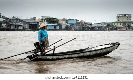 CAN THO, VIETNAM - JULY 29 2013: Vietnamese lady steers her boat in the rain towards the Phong Dien floating market in the Mekong delta 20km south west of Can Tho