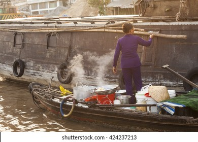 Can Tho, Vietnam - March 13, 2016: Vietnamese Woman  on a wood boat with smoking pots on Cai Rang floating market in the Mekong Delta. Sunset light