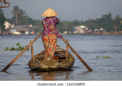 Can Tho, Vietnam - May 17, 2018: Senior lady wearing colorful clothes and rowing on a wooden boat in the area of Mekong Delta. Credit: Dino Geromella/Shutterstock
