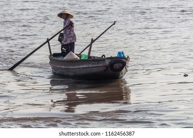 Can Tho, Vietnam - May 17, 2018: A vietnamese woman driving a boat on the Mekong river