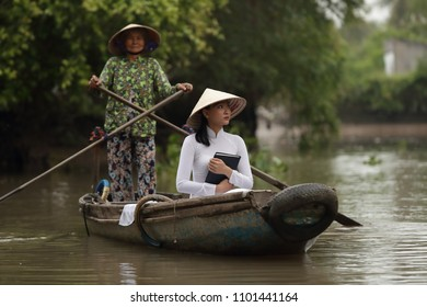 Can Tho, Vietnam-April 7, 2018: Traditionally dressed young Vietnamese woman takes a boat tour with an old boat woman on Mekong River