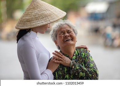 Can Tho, Vietnam-April 7, 2018: Traditionally dressed young Vietnamese woman cares  her grandmother in the riverside Mekong Delta.