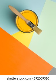 Can of yellow paint and brush on colourful geometrical background.  Renovation theme  with copy space