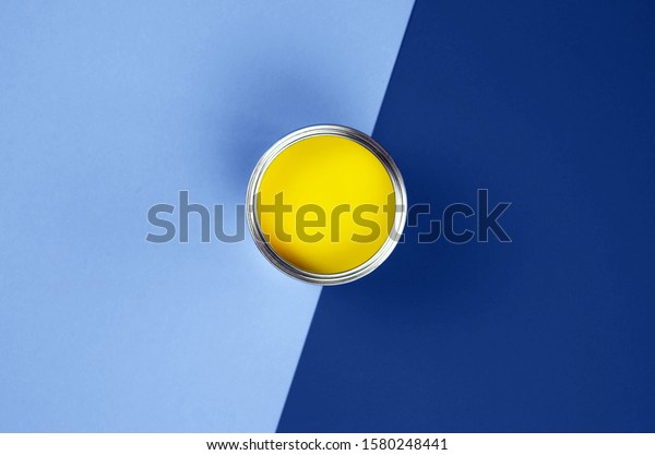 Can of yellow paint on a classic blue background.