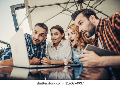 Can you believe this. Stunned smiling ladies and bearded men looking at notebook computer. Company sitting at the table