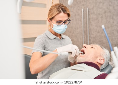 Can you finish it faster. Concentrated tense handsome senior man lying in dentists chair and holding his mouth open while dentist examining his dental health. Stock photo