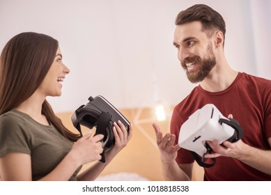 Can you imagine. Low angle of happy cheerful vigorous couple staring at each other while carrying VR glasses and laughing
