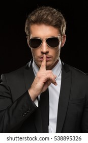 Can you keep a secret? Vertical studio shot of a handsome young secret service special agent wearing a suit and sunglasses shushing with his finger to his lips asking for silence on black background
