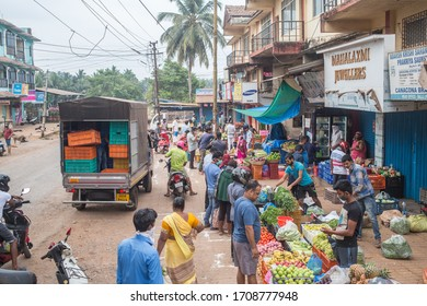 Canacona, Goa, India - April 18 2020:  People at a vegetable and fruit market in the morning with social distancing markers on the ground during the corona lockdown in India.