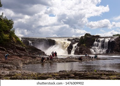 Lévis, Québec, Canada, August 11, 2019 - People enjoying the view of the impressive 115-foot tall Chaudière River Falls during a beautiful sunny summer afternoon