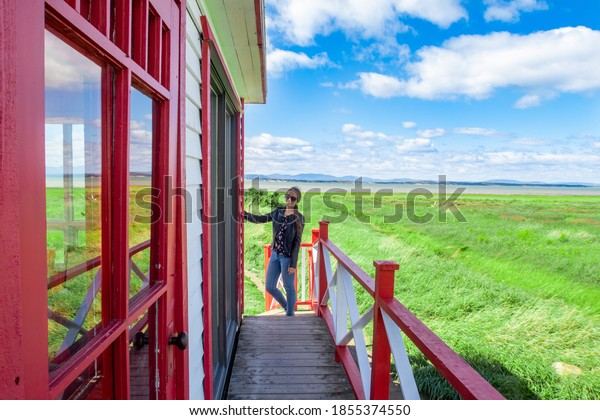 Saint-André-de-Kamouraska, Canada - August 2020 : young woman posing next to a red and white lighthouse